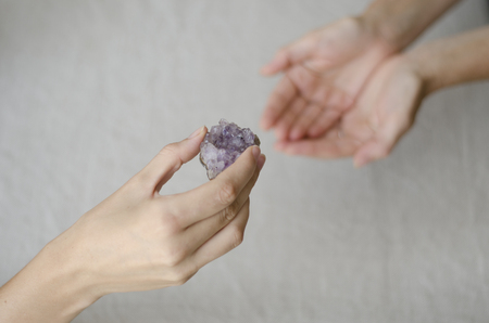 Womans hands giving an amethyst crystal in another womans hands in healing gesture. Stock Photo - 25131139