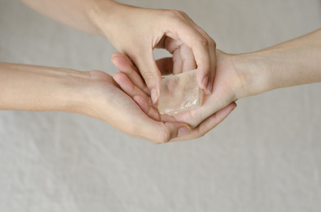 Womans hands giving a quartz crystal in healing gesture, with copy space room for text
