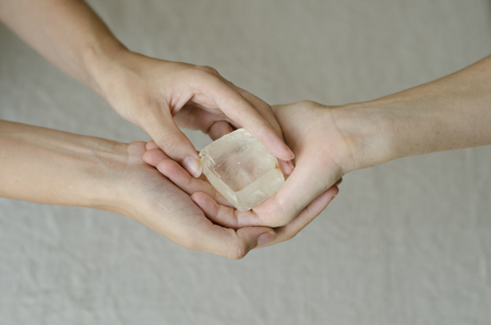 Womans hands holding and placing a quartz crystal in another womans hands in healing gesture. Stock Photo