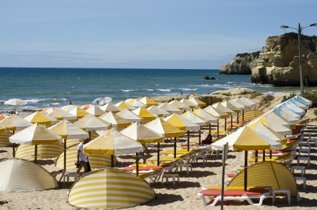 Striped sunshades and beach umbrellas on a blue flag beach in the Algarvegg