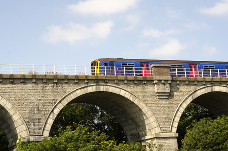 A brightly coloured train  going over old stone bridge above tree tops, uk Editorial