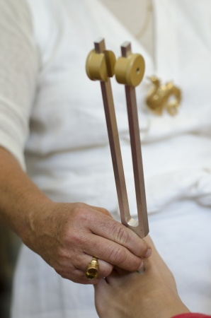 Close up of practitioner giving healing tuning fork treatment.