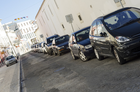 A diagonal line of cars parked along back street of white mediterranean buildings, with Hotel flags in the background.