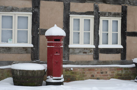 settled: A red British post box coverd with snow Stock Photo
