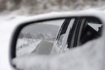 Snow covered hills and road in the rear view mirror of a car Stock Photo