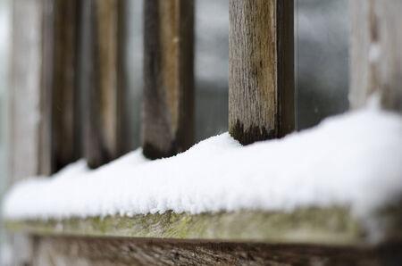 settled: Snow settled on the bottom of a wooden window frame
