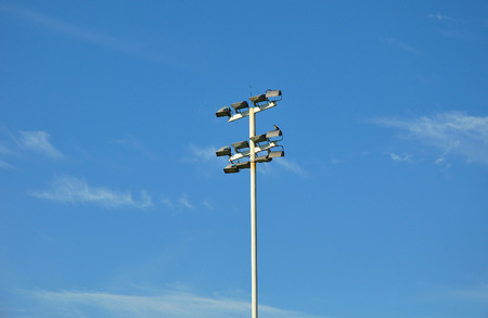 stadium lights: Stadium lights with bird against blues sky and white clouds