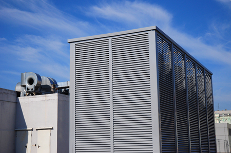Industrial air conditioning and ventilation systems on the sreet against blue sky with white clouds