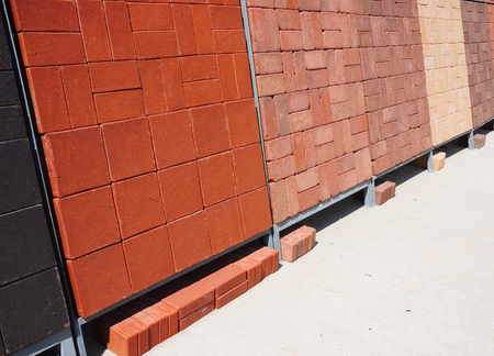 pavers: Stacks of various and for sale. Building and construction materials, colored concrete pavers paving stone, bricks, and patio blocks organized on pallets for sale stored on metal shelves outdoors