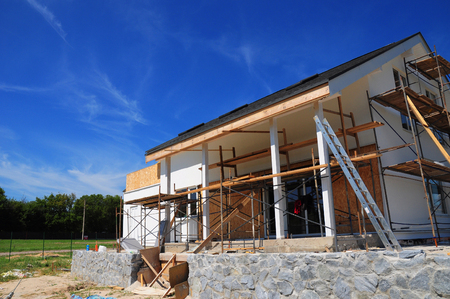 New frame house under construction, facade  against blue sky. Building new terrace Standard-Bild