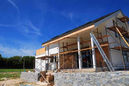 Nieuw frame huis in aanbouw, gevel tegen blauwe hemel. Nieuw terras opbouwen