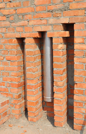 chimney corner: Installed in brick wall metal chimney for fireplace. Stainless steel chimney stove pipe installation.