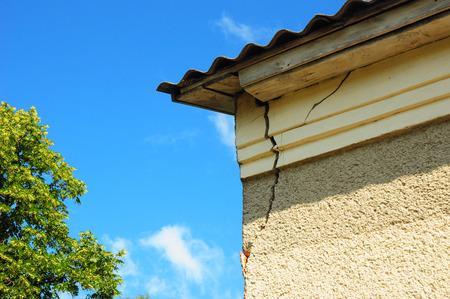 Architecture detail of damaged house corner dilapidated old building facade wall over blue sky background. Private abandoned home fall to ruin