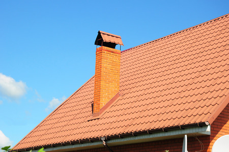 chimney corner: Faded red metal roof tile, rain gutter and chimney against blue sky. Bad roofing.