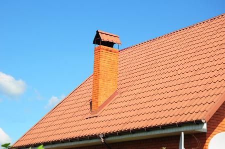 chimney corner: Faded tejas rojas de metal del techo, canal de la lluvia y la chimenea contra el cielo azul. Mala techos.