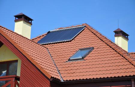 Energie-efficiëntie concept. Close-up van zonne-water-paneel verwarming op rode pannen dak van het huis met bliksembeveiliging en schoorsteen.