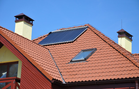 Energy efficiency concept. Closeup of solar water panel heating on red tiled house roof with lightning protection and chimney. Stock Photo