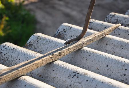 アスベスト瓦から正しく爪を抜く方法。ワーカー修復危険なアスベスト古い屋根瓦。屋根工事。