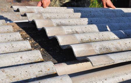peligro: Reparaci�n Roofer asbesto peligroso Old Roof Tiles. Reparacion de Techos Foto de archivo