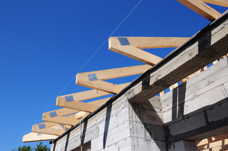 wooden joists: Installation of wooden beams at construction the roof truss system of the house