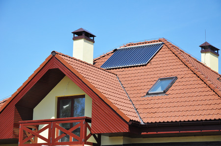 Solar water panel heating on red tiled house roof with lightning protection and chimney against blue sky