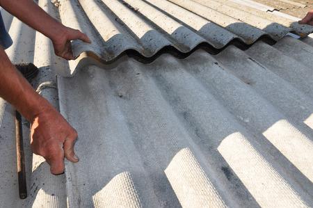 危険なアスベスト古い瓦を修理します。労働者は、アスベストの屋根帯状疱疹 - 手でクローズ アップをインストールします。1980 年代以降、国内建 写真素材