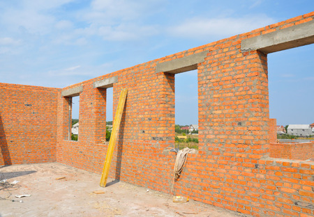 brick house: Interior of a unfinished red brick house under construction. Closeup on windows hole construction Stock Photo