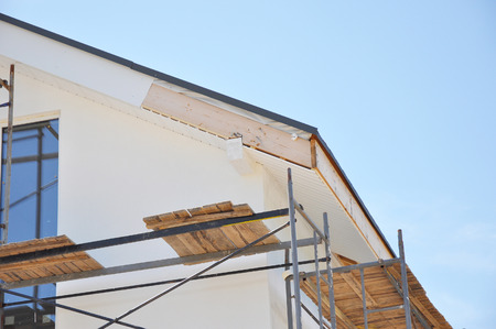 TRUSS: Corner of house with eaves, rafters, truss. Install softies and roof insulation detail. Roofing. Stock Photo