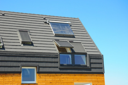 Closeup of Solar Water Panel Heating, Dormers, Solar Panels, Skylights, Ventilation and Air Conditioning Systems Installed on House Roof. Energy Efficiency New Passive House Building Concept.