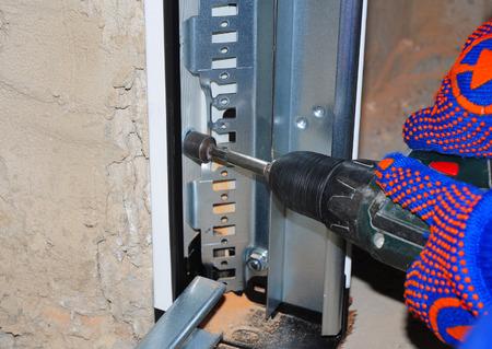 ガレージのドアのパネル取付け。プラスチックと金属のドア プロフィール パネルを壁にアタッチするドリルを使用している人。 写真素材