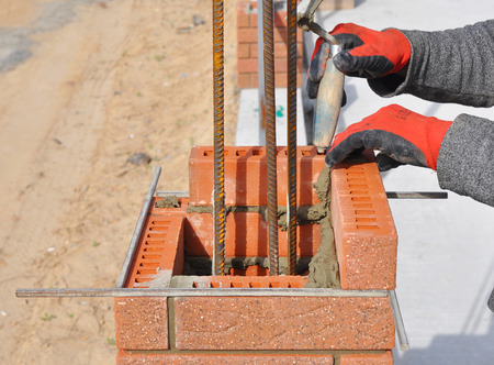 Bricklaying Closeup. Bricklayer hand holding a Putty Knife and Building a Brick Wall Column with Iron Bar Outdoor. Stock Photo