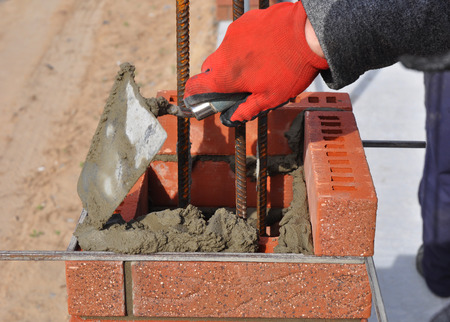 Bricklayer worker installing red blocks and caulking brick masonry joints exterior wall with trowel putty knife outdoor