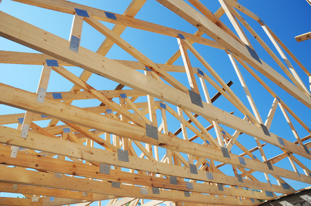 New residential construction home framing against a blue sky. Roofing construction. Wooden roof trusses construction Stockfoto