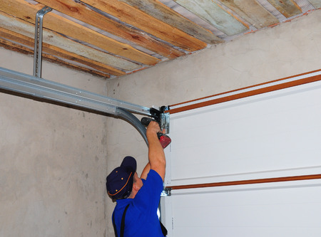 Contractor Installing Garage Door Post Rail and Spring Installation and Garage Ceiling. Spring Tension Lifts Metal Section Garage Door Panel that the Motor does not have to Lift Entire Weight. Stock Photo