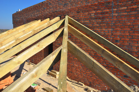 roofing membrane: Roofing Construction. Close up on wooden rafters, eaves, wooden beams installed on brick wall with bitumen waterproofing membrane and metal anchors attachment.