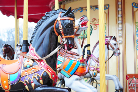 Beautiful horse carousel in a holiday park. Three horses on a traditional fairground vintage carousel. Merry-go-round with horses. Stock Photo
