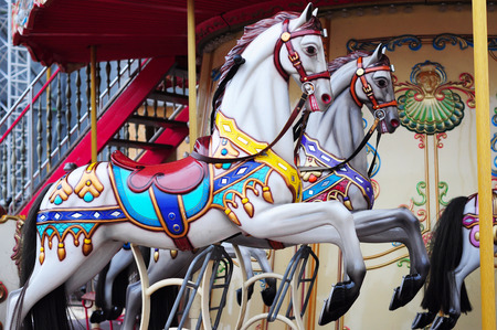 turnabout: Beautiful horse Christmas carousel in a holiday park. Two horses on a traditional fairground vintage carousel. Merry-go-round with horses.