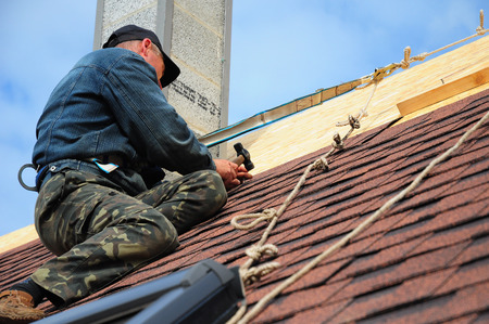 Roofing Contractor. Roofing Construction and Building New House with Modular Chimney, Skylights, Attic  Exterior. Roofers Install, Repair Asphalt Shingles or Bitumen Tiles on the Rooftop Outdoor