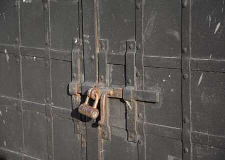 pawl: The old big padlock. Closed metal door with old lock