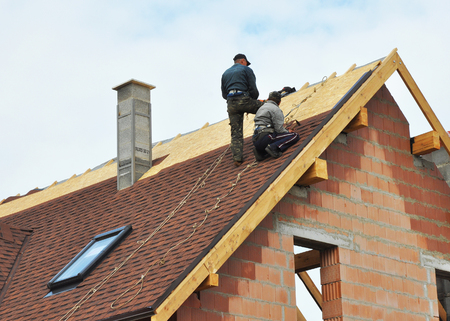 Building contractors putting the asphalt roofing. Roofers laying tiles on the roof while roofing a house outdoor. Roofers Install, Repair Asphalt Shingles or Bitumen Tiles on the Rooftop Outdoor. Roofing Construction.