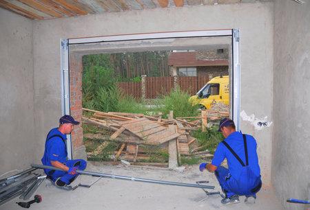 handtools: KIEV, UKRAINE - JULY 13, 2016: Contractors Installing Garage Door. Step by Step. Installing Garage Door Post Rail and Spring Installation.