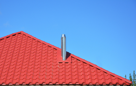 New red tiled roof with metal chimney house roofing construction exterior. Stockfoto