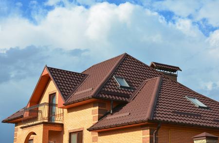 Nueva construcción de techos con claraboyas en el ático, sistema de canales de lluvia, ventanas de techos y protección del techo contra la nieve, exterior de la casa de guardia de nieve.