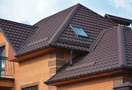 roofing system: New roofing construction with attic skylights, rain gutter system, roof windows and roof protection from snow board, snow guard exterior. Modern House Construction. Hip and Valley roofing types. Roofing Construction.