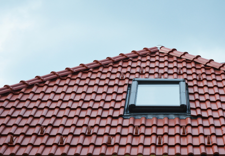 Attic skylight window on red ceramic tiles house roof outdoor. Attic Skylights Home Design Ideas Exterior. Reklamní fotografie