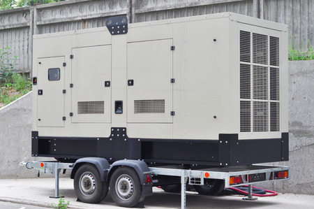 Commercial backup generator. A standby generator is a back-up electrical system that operates automatically.  A standby power system may include a standby generator, batteries and other apparatus. Stock Photo