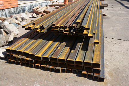 Rust steel channel bunch on house construction site outdoor. Steel beams for roofing. Stock Photo