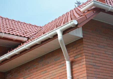 雨樋防水の家問題領域にビューを閉じます。雨樋、側溝、雨樋、雨樋プラスチック ・排水。Guttering ダウン パイプ継手 写真素材