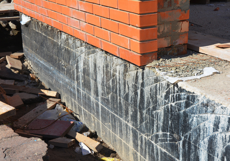 Waterproofing foundation walls. Foundation Waterproofing and Damp proofing Coatings.Waterproofing house foundation with spray on tar. House insulation, waterproofing basement and foundations
