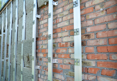 Brick house wall repair and rock wool or  mineral wool  wall insulation. External wall insulation - Save energy. Stock Photo